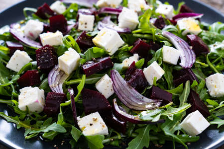 Beetroot salad with feta cheese on wooden table