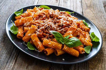 Tortiglioni with tomato sauce, meat and parmesan on wooden background