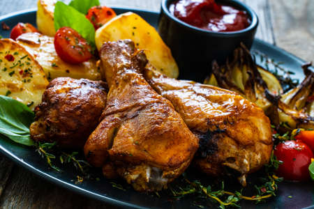 Barbecue chicken drumsticks with vegetables on wooden table