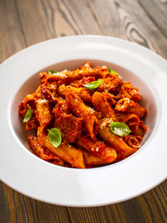 Penne with meat, tomato sauce and vegetables on white background