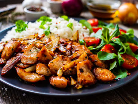 Chicken meat with rice and vegetables on wooden table