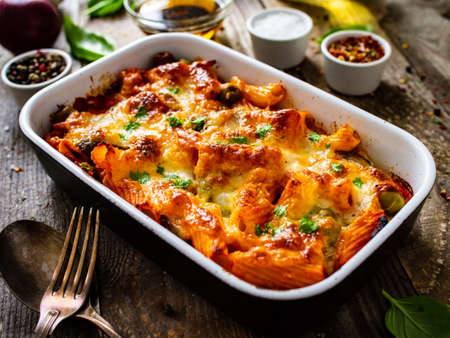 Pasta casserole with minced meat, mozzarella cheese and vegetables on wooden table Banque d'images