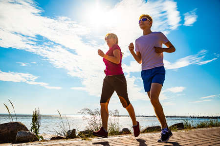 Woman and man running by sea shore Imagens