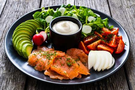 Breakfast - smoked salmon, avocado, garlic creamy dip and vegetable salad on wooden table