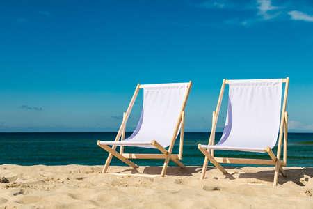 Empty beach - two empty deckchairs on empty beach