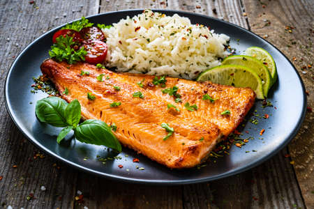 Fried salmon steak with rice and vegetables on wooden table
