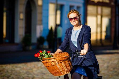 Urban biking - woman riding bike on city street 스톡 콘텐츠