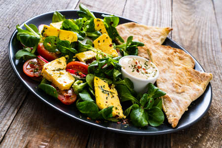 Fresh salad - blue cheese, cherry tomatoes, vegetables and homemade bread on wooden background