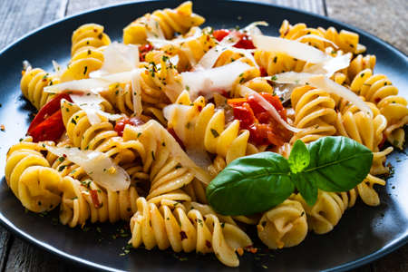 Pasta with parmesan and vegetables on wooden background