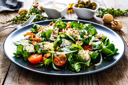Fresh salad - blue cheese, cherry tomatoes, vegetables and walnuts on wooden background