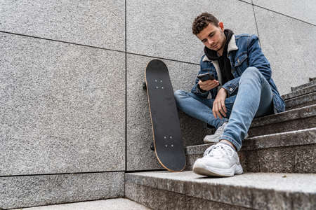 Young man with skateboard sitting on stairs 免版税图像