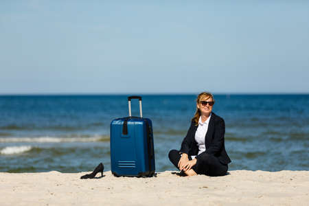 Woman with suitcase sitting on beach