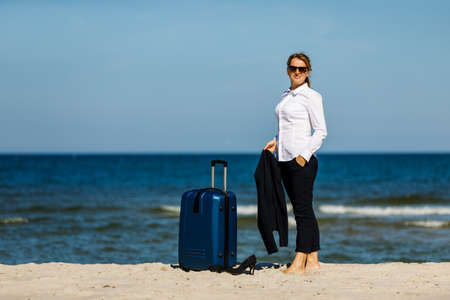 Woman with suitcase walking on beach