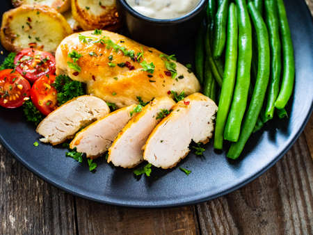 Roast chicken fillets with green beans and fried potatoes on wooden table