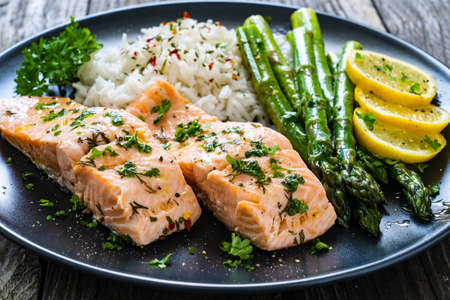 Steamed salmon fillet with basmati rice, asparagus and vegetables on wooden table