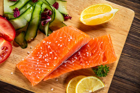 Fresh raw salmon steaks with vegetables on wooden board