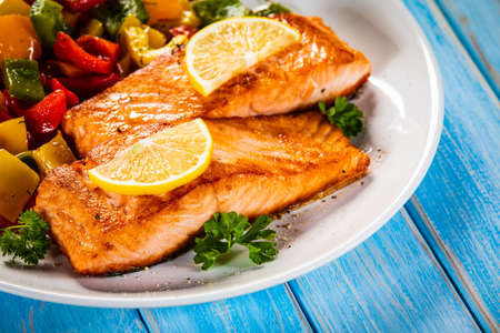 Fried salmon steaks with lemon and bell pepper served on wooden table