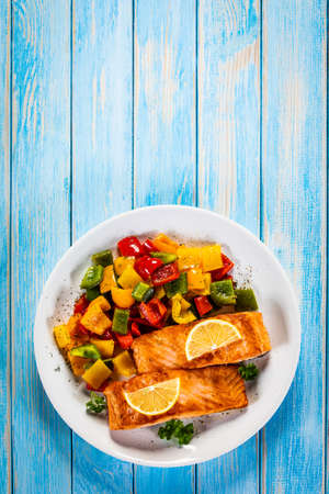 Fried salmon steaks with lemon and bell pepper served on wooden table Banque d'images