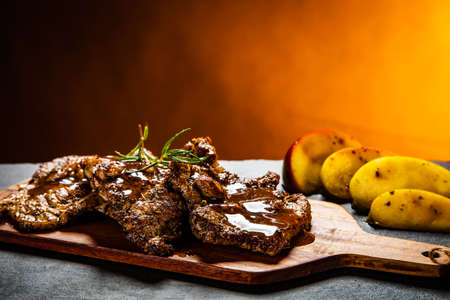 Barbecue pork neck with apples on wooden board