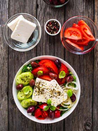 Fresh Greek salad - feta cheese, tomatoes, cucumber, red pepper, black olives and onion on wooden table