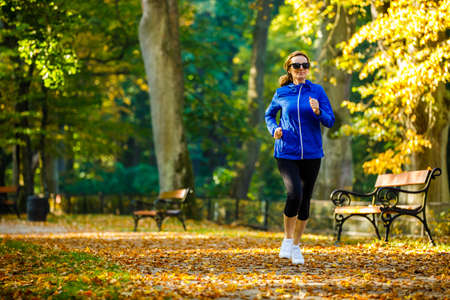 Healthy lifestyle - woman running in city park Imagens