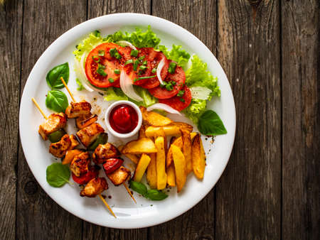 Skewers - grilled meat with French fries and fresh vegetables on wooden background