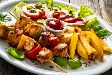 Skewers - grilled meat with French fries and fresh vegetables on wooden background Foto de archivo