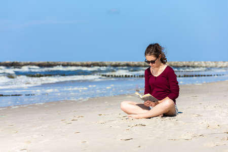 Teenage girl reading book sitting on beach