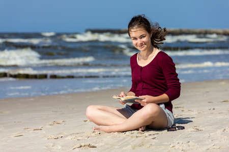 Teenage girl reading book sitting on beach Reklamní fotografie