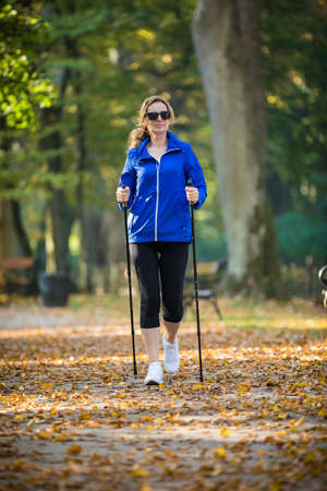 Nordic walking - middle-age woman training in city park