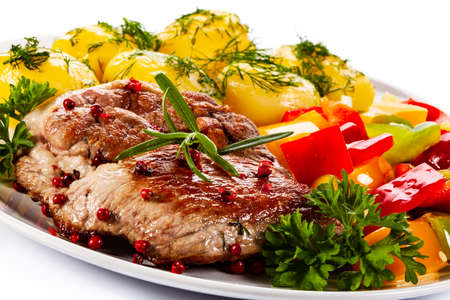 Grilled steak with boiled potatoes and vegetables on white background