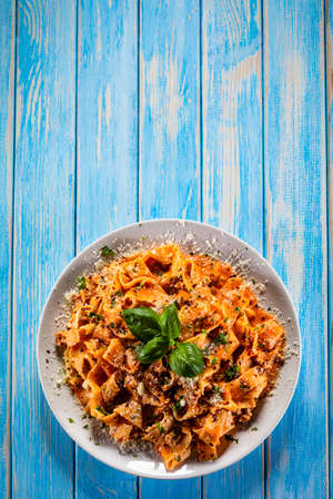 Tagliatelle with marinara sauce, meat and parmesan on wooden table