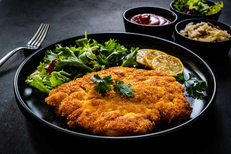 Breaded fried pork chop and fresh vegetables on black table