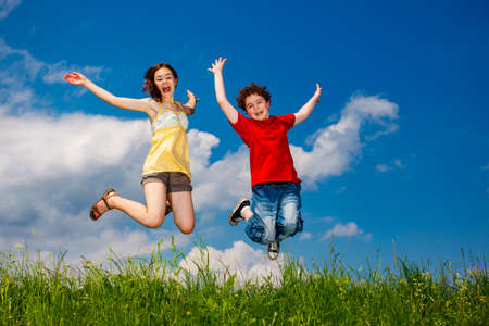 Girl and boy running, jumping against blue sky