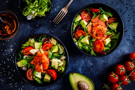 Salmon salad - smoked salmon with avocado and mix of vegetables on black wooden table Reklamní fotografie