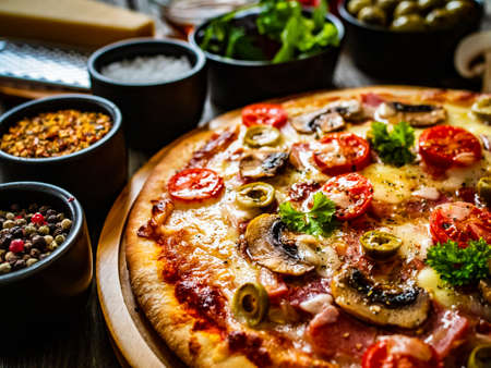 Pizza with champignons, ham, tomatoes, olives, parmesan and mozzarella on wooden background
