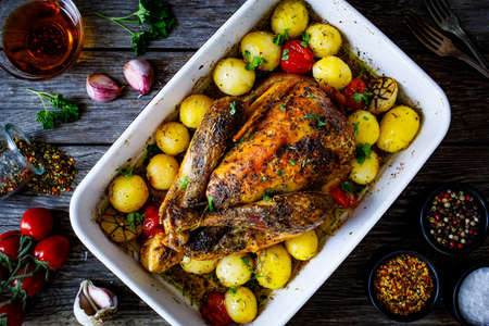 Whole roast chicken with vegetables on wooden table Stock Photo