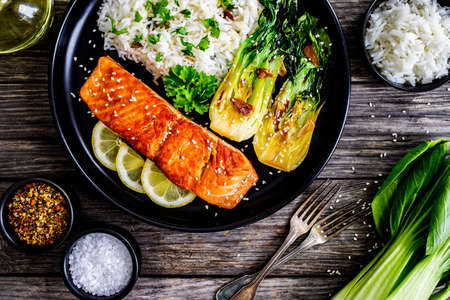 Fried salmon steak with lemon, jasmine rice and fried pak choi cabbage served on wooden table
