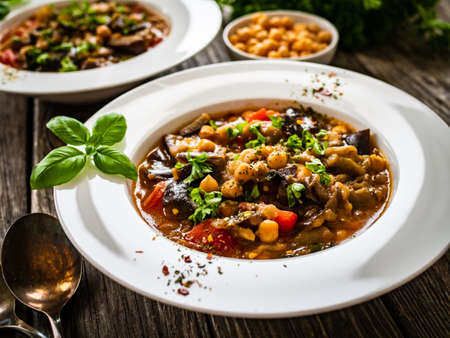 Delicious stew - aubergine with tomatoes and chickpeas on wooden table