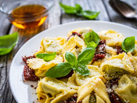 Tortelloni stuffed with ricotta cheese, basil pesto and vegetables on wooden table