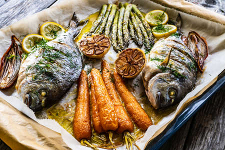 Sheet pan dinner - roasted whole sea bream with asparagus, carrots, lemon, rosemary and garlic on cooking pan on wooden table