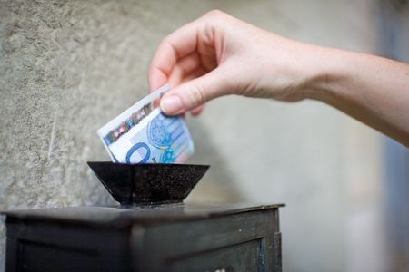 Close-up: Inserting a banknote into offertory box. Very small DOF. Stock Photo