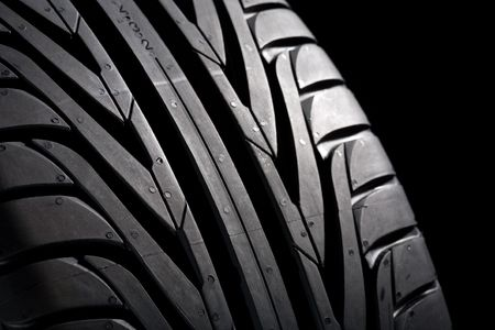 Summer tire (22545R17) on black background. Its a new one. Close-Up. Stock Photo