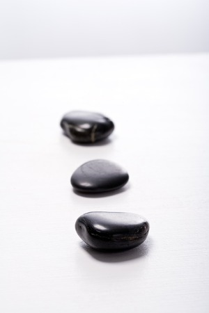 Three smooth, black Zen-Stones (Pebbles) in a row. Focus on front stone. Imagens