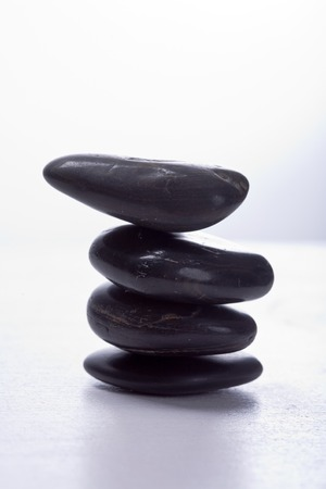 stapled: Four round, smooth black stones stapled. Zen-Style. White background. Reassuring.
