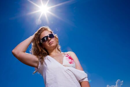 Attractive woman Looking cool with big sunglasses, casual wear and bikini into camera. Deep blue sky with Lensflares