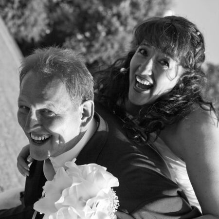 bridal couple: Happy and laughing bridal couple. He carries her. Diagonal view, square format, monochrome. They are beaming for joy!