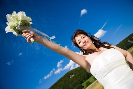 diagonally: Fancy Perspective. Bride holds her bridal bouquet on outstretched arm. Deepblue sky as background. Sunny weather. Adult bride.