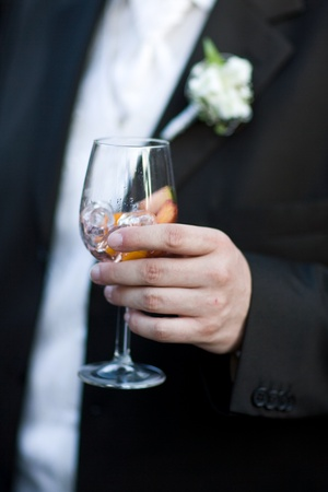 shallow dof: Bridegroom holding a glass of wine-cooler with icecubes. Close-Up. Shallow DOF!