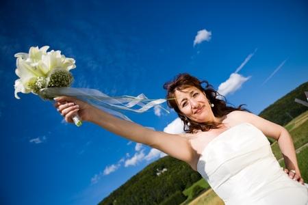 sprawled: Fancy perspectivas. Bride tiene su ramo nupcial en brazo extendido. Deepblue cielo como fondo. Tiempo soleado. Adultos novia.